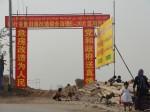 """Auf dem Spruchbanner lässt die """"Projektdienststelle für die Rundumerneuerung maroden Wohnraums in Kashgar"""" die Anwohner wissen: """"Die Rundumerneuerung maroden Wohnraums kommt dem Volk zu Gute - Partei und Regierung sorgen sich um euch"""". ©Gesa Stupperich"""
