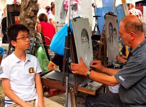 Ein französischer Zeichner fertigt in Paris ein Porträt von einem jungen chinesischen Touristen an. © Wikimedia Commons, zoetnet